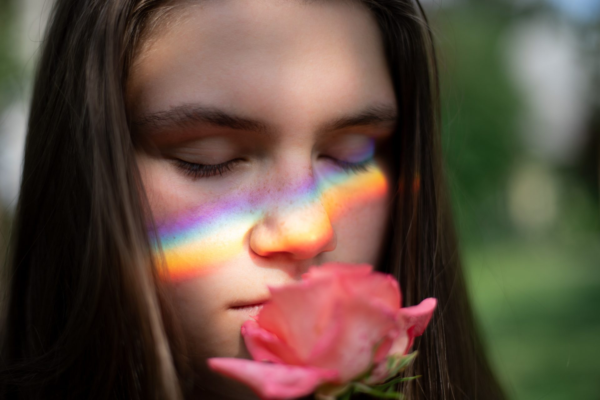 Woman sniffing a rose with a rainbow on her face